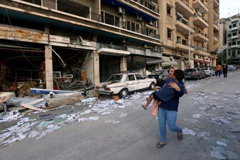 Una mujer corre con un niño tras las explosiones en Beirut