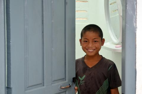 Un niño de Laos sonríe en el baño del colegio